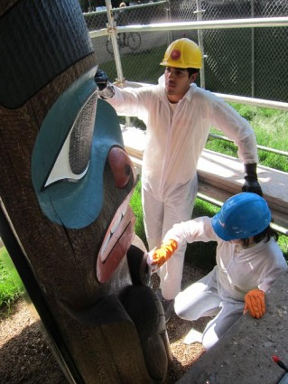 Conservation technicians Nicole Passerotti and Mauricio Antunano apply protective coating